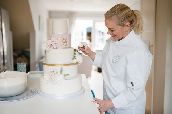 person decorating a wedding cake