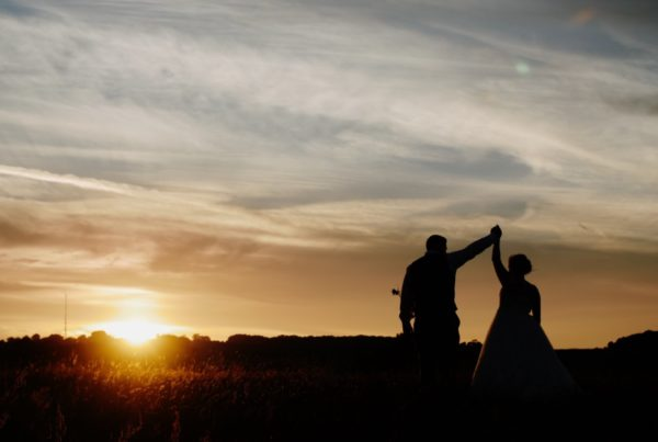 bride and groom with a sunset