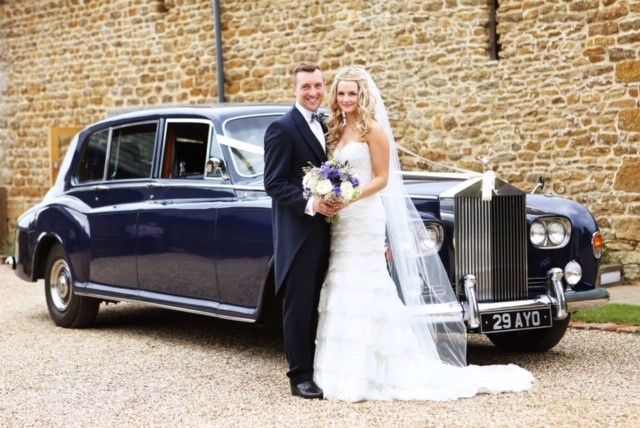 Bride and groom in front of a navy car
