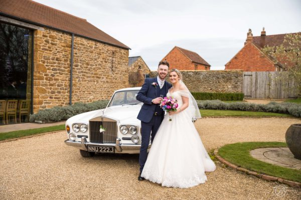 Bride and groom in front of a white car