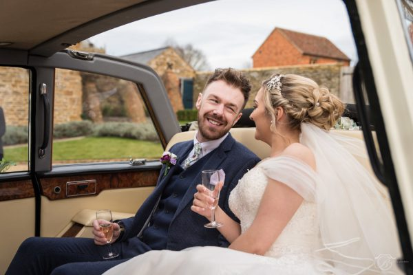 Bride and groom in the back of a car