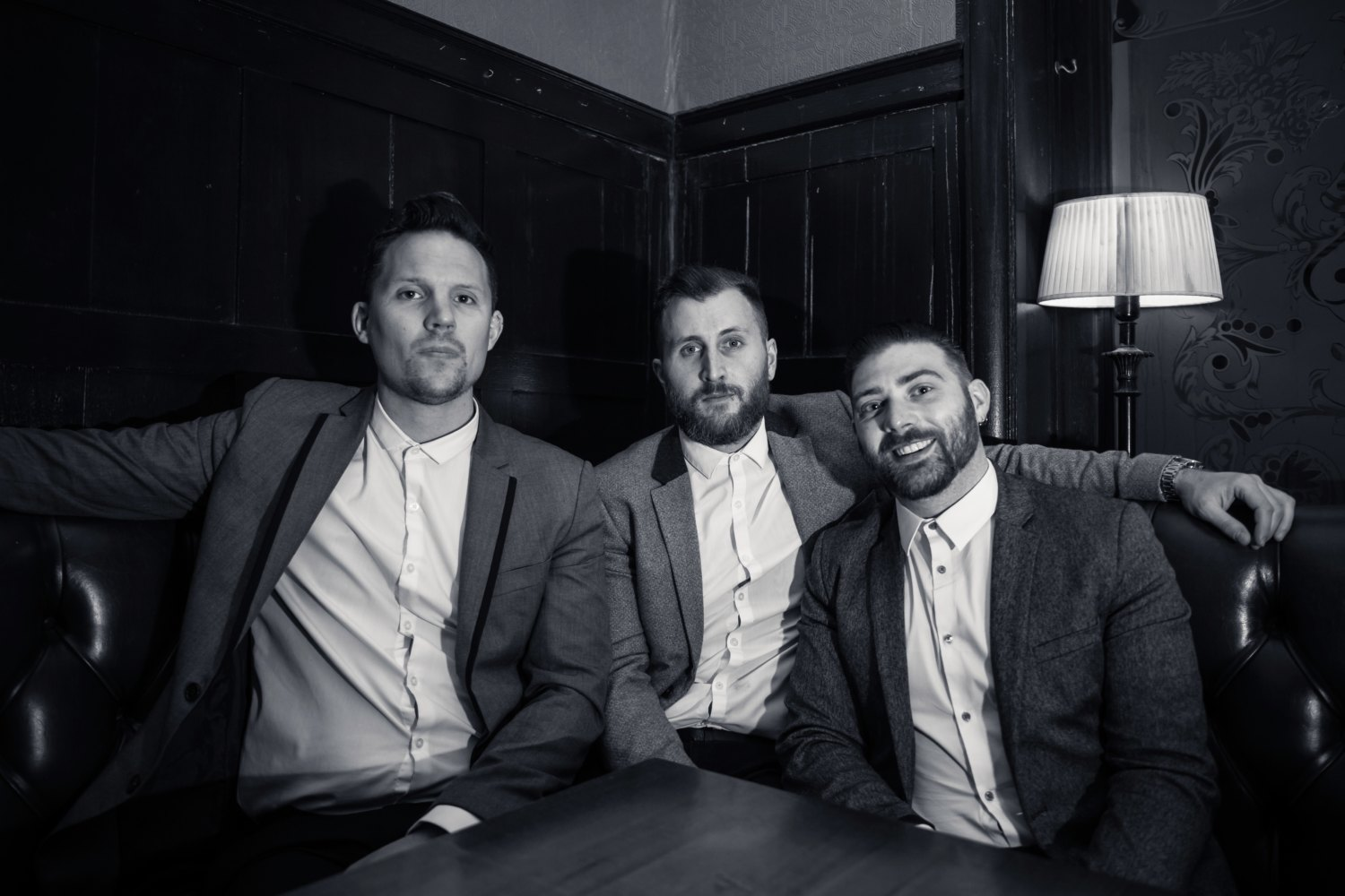 Three men sat on a couch