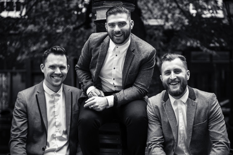Three men in suits posing