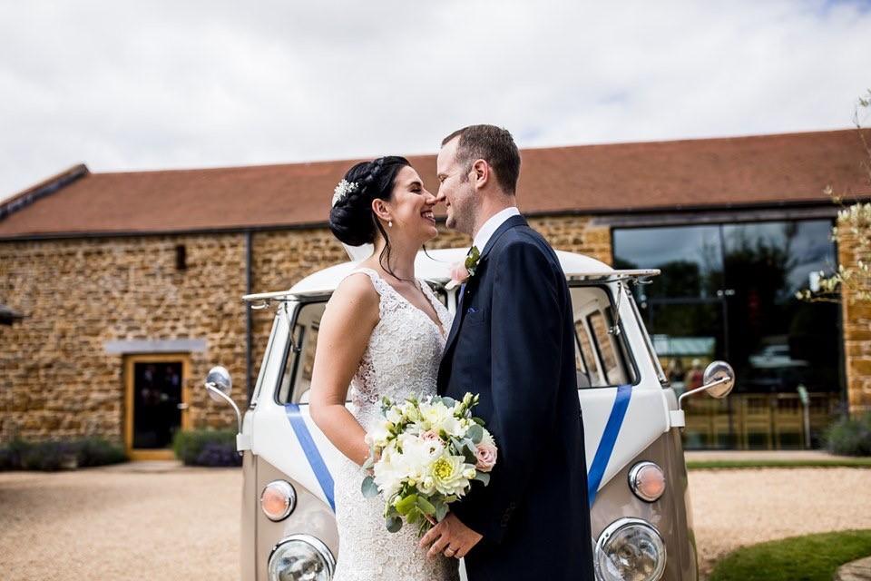 Bride and groom standing in front of a VW van