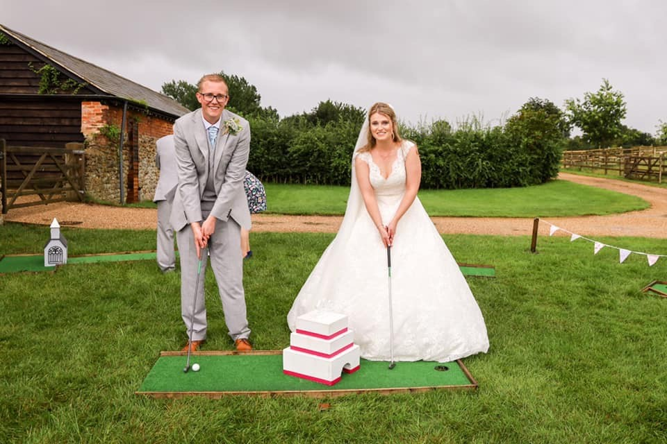 Bride and groom playing mini golf