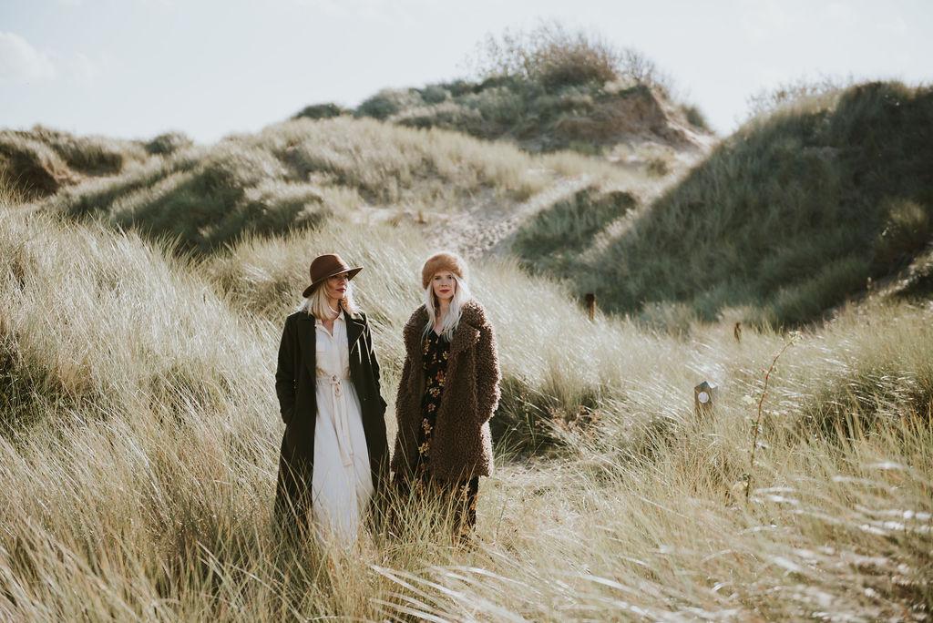 Two women standing in sand dunes