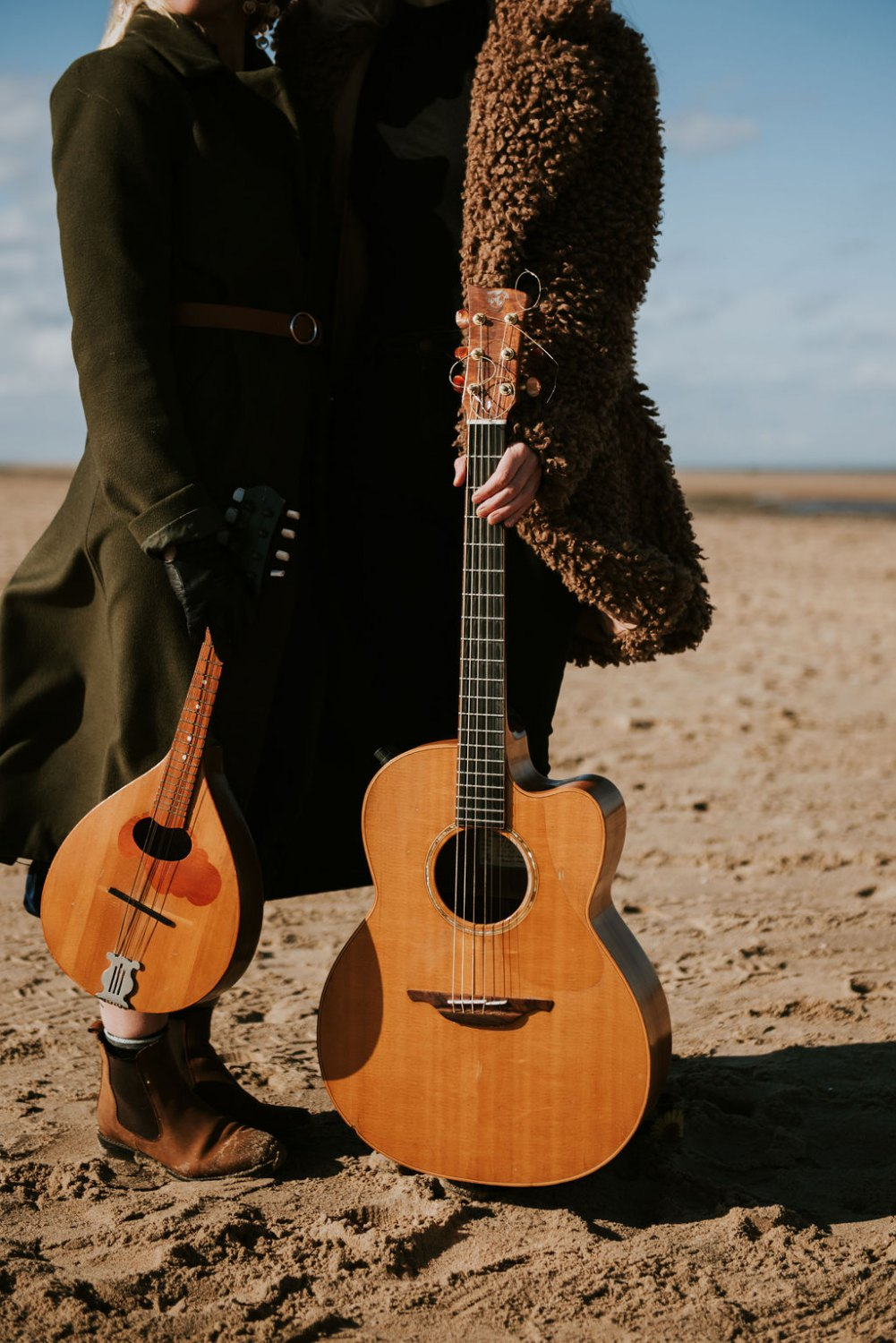 Two people holding guitars at the beach
