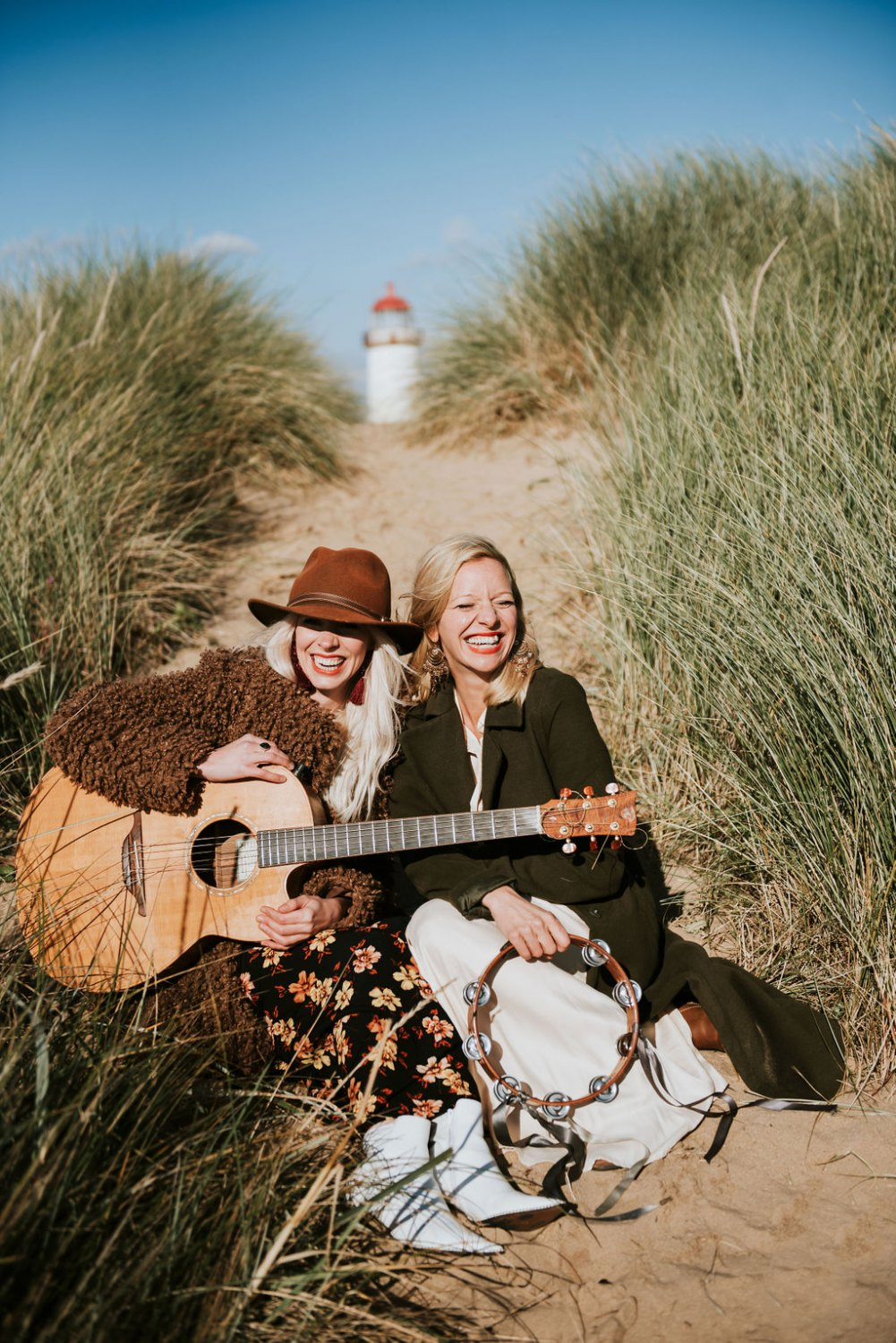 Two women with a guitar on the beach