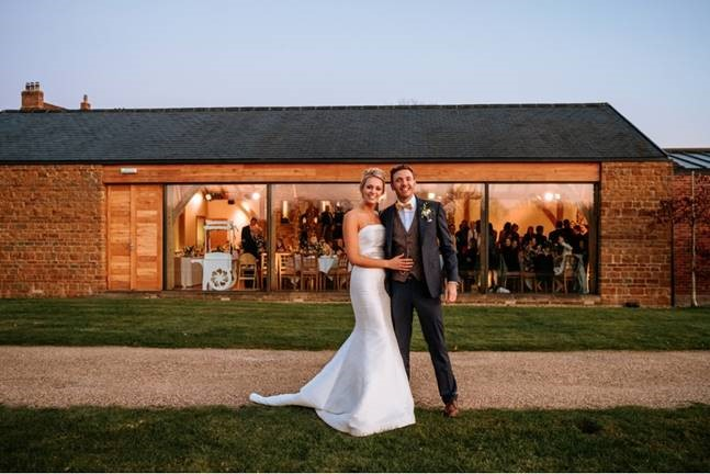 Bride and groom outside a converted barn