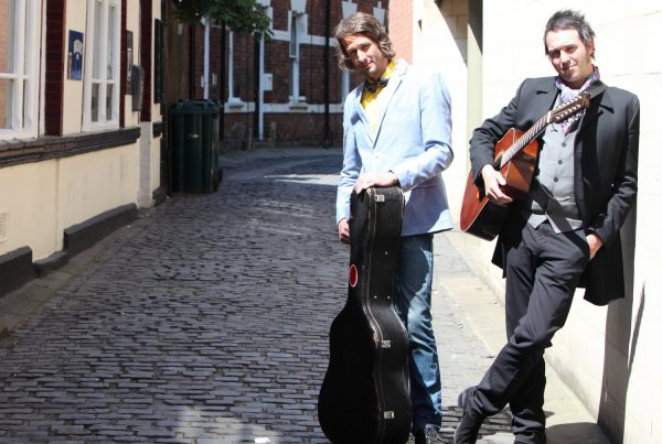Two men with guitars posing in an alley